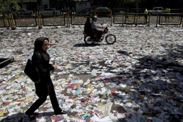 People walk over electoral leaflets, covering the street after Friday prayers in Tehran, Iran, Friday, June 7, 2013. Iranian Presidential election will be held on June 14, 2013. (AP Photo/Ebrahim Noroozi)