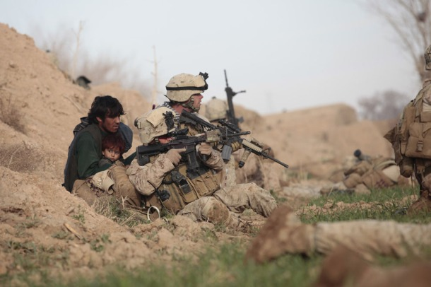 U.S. Marines from Bravo Company, 1st Battalion, 6th Marines, Lance Corporal Chris Sanderson, (rear) and Sergeant Travis Dawson, (front) protect an Afghan man and his child after Taliban fighters opened fire in the town of Marjah, in Helmand province, on February 13, 2010. U.S.-led NATO troops launched an offensive against the Taliban's last big stronghold in Afghanistan's most violent province and were quickly thrown into a firefight with the militants. (Reuters/Goran Tomasevic)